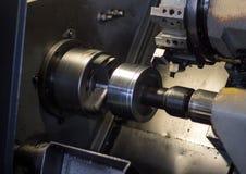 O torno do CNC retira a parte da polia do workpiece do metal, torno moderno para o metal que processa, close-up, máquina fotografia de stock