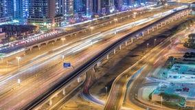 O tráfego de Sheikh Zayed Road no porto de Dubai e nos lagos Jumeirah eleva-se timelapse da noite dos distritos filme