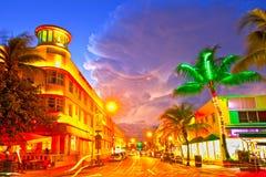 O tráfego movente, os hotéis iluminados e os restaurantes no por do sol no oceano conduzem, Imagens de Stock Royalty Free