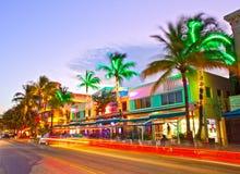 O tráfego movente, os hotéis iluminados e os restaurantes no por do sol no oceano conduzem Fotografia de Stock Royalty Free