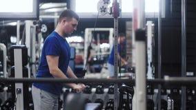 O tríceps atrativo considerável da corda do cabo do homem abaixa o exercício ao dar certo no gym filme