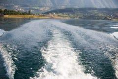 O traço tormentoso de barco de motor que cruza a esmeralda molha Fotos de Stock
