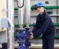 O trabalhador abre uma válvula na planta imagem de stock
