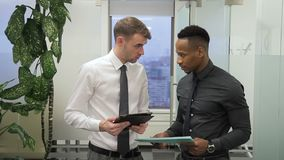 O trabalhador africano masculino está falando a seu chefe caucasiano sobre o relatório no escritório video estoque
