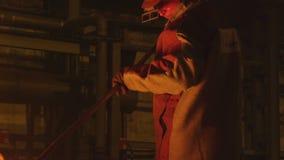 O trabalhador ajunta para fora o metal da cubeta com faíscas filme
