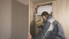 O trabalhador ajusta as portas no armário e instala o hardware, acessórios vídeos de arquivo