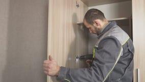 O trabalhador ajusta as portas no armário e instala o hardware, acessórios video estoque