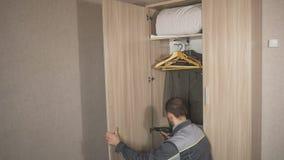 O trabalhador ajusta as portas no armário e instala o hardware, acessórios filme