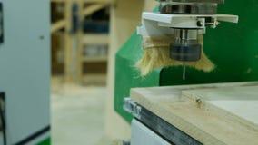O trabalhador ajusta o programa com o painel de controle em uma máquina automática do woodworking com um CNC video estoque