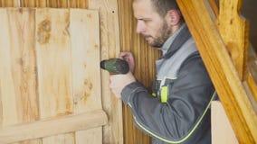 O trabalhador ajusta-se - acima de uma porta feito a si próprio em um interior de madeira filme