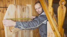 O trabalhador ajusta-se - acima de uma porta feito a si próprio em um interior de madeira medidas com uma régua uma entrada e uma vídeos de arquivo