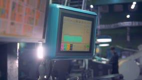 O trabalhador ajusta-se - acima do equipamento industrial usando o écran sensível do computador filme