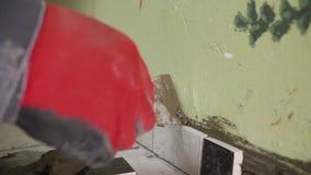 O trabalhador ajusta telhas pequenas na parede na cozinha Suas mãos estão colocando a telha no esparadrapo tiro do stedikam video estoque