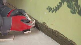 O trabalhador ajusta telhas pequenas na parede na cozinha Suas mãos estão colocando a telha no esparadrapo tiro do stedikam vídeos de arquivo