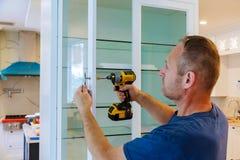 O trabalhador ajusta um punho novo no armário branco com uma chave de fenda imagem de stock royalty free