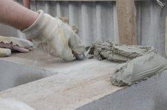 O trabalhador alinha com os cinderblocks de um tijolo da configuração da espátula Imagens de Stock Royalty Free