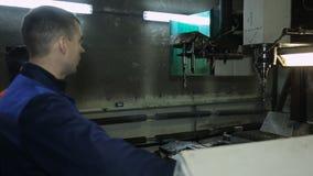 O trabalhador ao lado da máquina seleciona uma broca através do painel de controle vídeos de arquivo