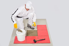 O trabalhador aplica o adesivo da telha com Trowel entalhado imagens de stock