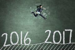 O trabalhador asiático salta no quadro-negro com 2017 Fotos de Stock Royalty Free
