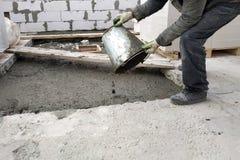 o trabalhador auxiliar derrama fora de um almofariz líquido do cimento da cubeta no assoalho entre os assoalhos da casa fotografia de stock royalty free