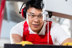 O trabalhador chinês viu sobre na fábrica industrial fotografia de stock