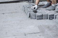 O trabalhador coloca telhas cinzentas do pavimento do granito no local marcado Arranjo do ambiente urbano Reparo de estradas de c imagens de stock royalty free
