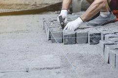 O trabalhador coloca telhas cinzentas do pavimento do granito no local marcado Arranjo do ambiente urbano Reparo de estradas de c fotografia de stock