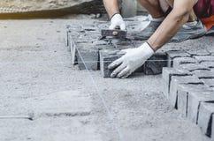 O trabalhador coloca telhas cinzentas do pavimento do granito no local marcado Arranjo do ambiente urbano Reparo de estradas de c fotos de stock