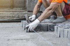 O trabalhador coloca telhas cinzentas do pavimento do granito no local marcado Arranjo do ambiente urbano Reparo de estradas de c foto de stock royalty free