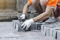 O trabalhador coloca telhas cinzentas do pavimento do granito no local marcado Arranjo do ambiente urbano Reparo de estradas de c fotos de stock royalty free