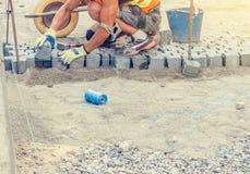 O trabalhador coloca telhas do granito no pavimento fotos de stock royalty free