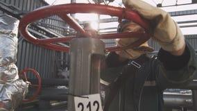 O trabalhador com bigode gerencie a válvula contra as tubulações de gás vídeos de arquivo