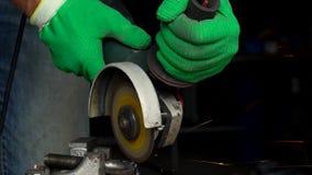 O trabalhador com a máquina de moedura angular está cortando o metal vídeos de arquivo