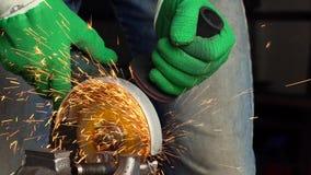 O trabalhador com a máquina de moedura angular está cortando o metal Movimento lento filme