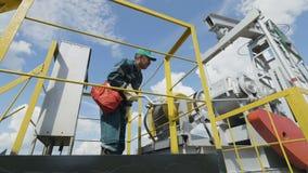 O trabalhador com saco vermelho verifica o equipamento na bomba Jack video estoque