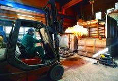 O trabalhador conduz a empilhadeira a endurecer o alto-forno com componentes de aço de incandescência foto de stock royalty free