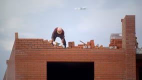 O trabalhador constrói a parede dos tijolos construtor na construção que faz a alvenaria o construtor no canteiro de obras faz a  vídeos de arquivo