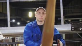 O trabalhador controla a dobradura da folha de papel na linha de produção vídeos de arquivo