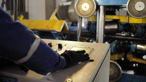 O trabalhador controla a máquina industrial do console filme