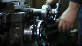 O trabalhador controla a roda do ajuste da máquina do torno filme