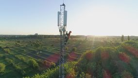 O trabalhador da alta altitude na torre de comunicação da antena faz uma chamada móvel e mostra o polegar acima na luz solar, opi vídeos de arquivo