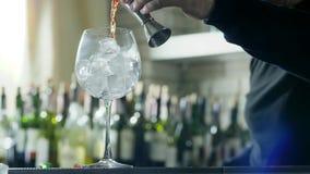 O trabalhador da barra adiciona o uísque ao vidro com os cubos de gelo no close-up da mesa em fundo unfocused das garrafas filme