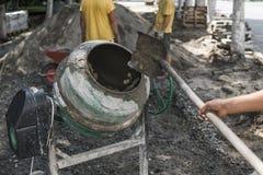 O trabalhador da construção adiciona ingredientes para misturar no misturador concreto no terreno de construção usando a pá duran imagens de stock