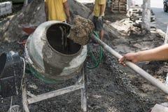 O trabalhador da construção adiciona ingredientes para misturar no misturador concreto no terreno de construção usando a pá duran imagem de stock royalty free