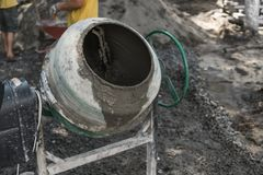O trabalhador da construção adiciona ingredientes para misturar no misturador concreto no terreno de construção usando a pá duran fotos de stock royalty free