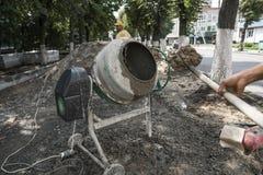 O trabalhador da construção adiciona ingredientes para misturar no misturador concreto no terreno de construção usando a pá duran fotografia de stock
