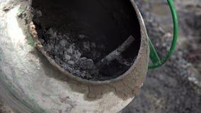 O trabalhador da construção adiciona ingredientes para misturar no misturador concreto no terreno de construção usando a pá duran vídeos de arquivo