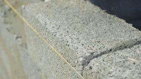 O trabalhador da construção constrói a parede de tijolo, opinião do close up no canteiro de obras filme