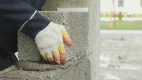 O trabalhador da construção constrói a parede de tijolo, opinião do close up no canteiro de obras video estoque