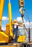 O trabalhador da construção durante o levantamento trabalha por um guindaste móvel foto de stock